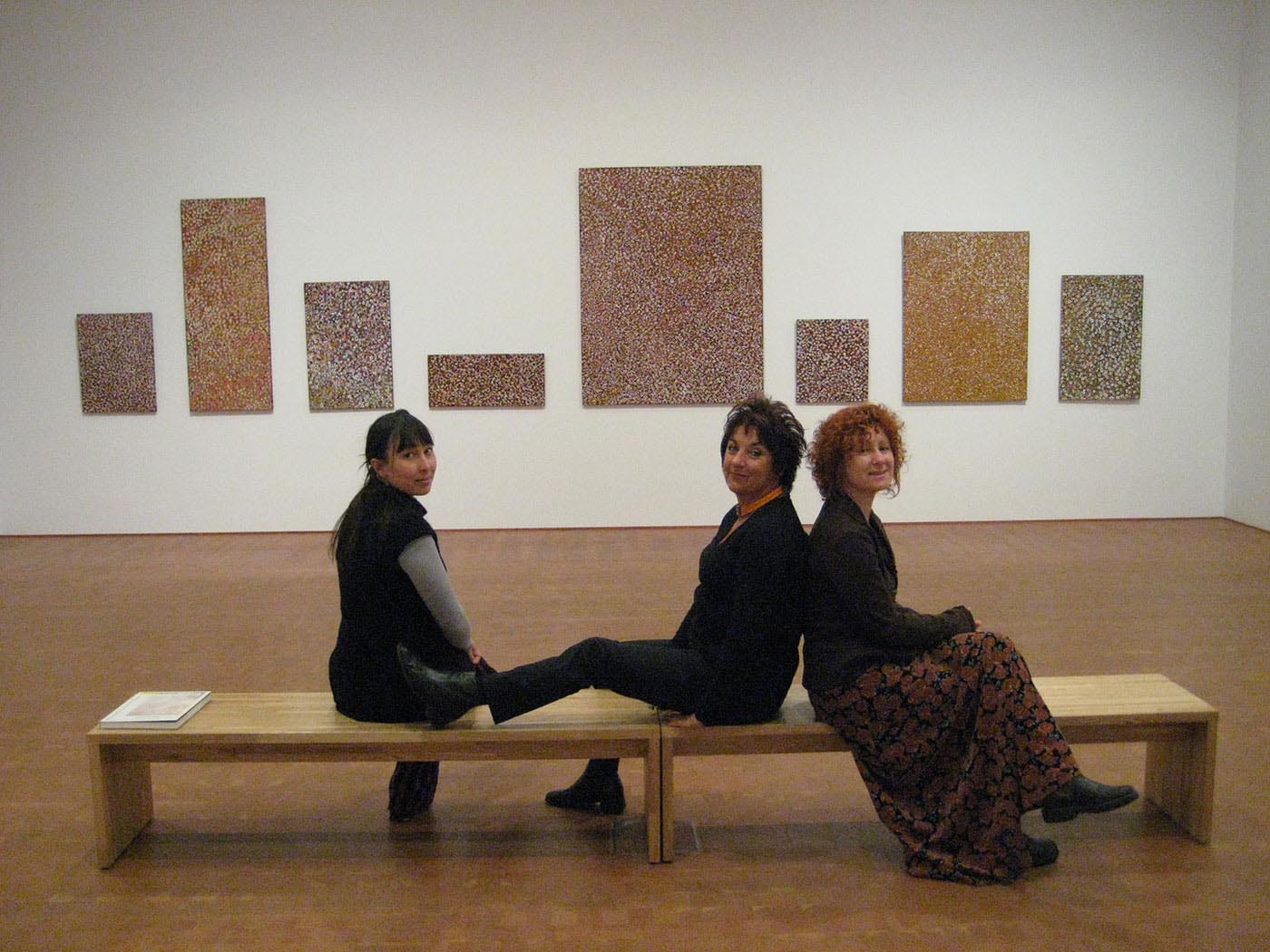 Three women sitting on a bench in a gallery space with paintings mounted in the wall. - click to view larger image