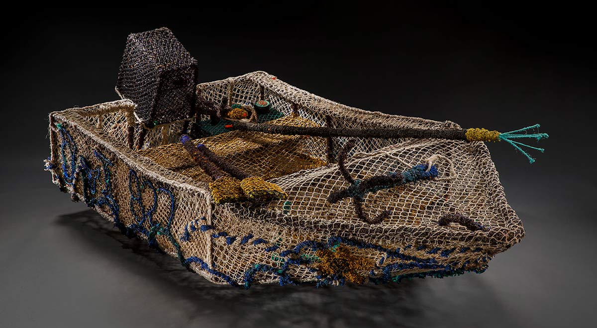 A dinghy sculpture made from fishing nets and ropes. It includes sculptural representations of an outboard motor, anchors, a spear, oars and fuel tank.