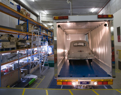 A colour photograph showing an early model Holden car being loaded into a van for transport to a storage facility. The van is at the right side of the photograph, with its rear end closest to the camera. The rear door is open, and inside can be seen the rear of the Holden car. The van is parked in what appears to be a loading bay; large shelves at the left of the photograph hold a variety of objects, some of which are in boxes. On the concrete floor of the loading bay can be seen yellow stripes that appear to mark out safety zones.
