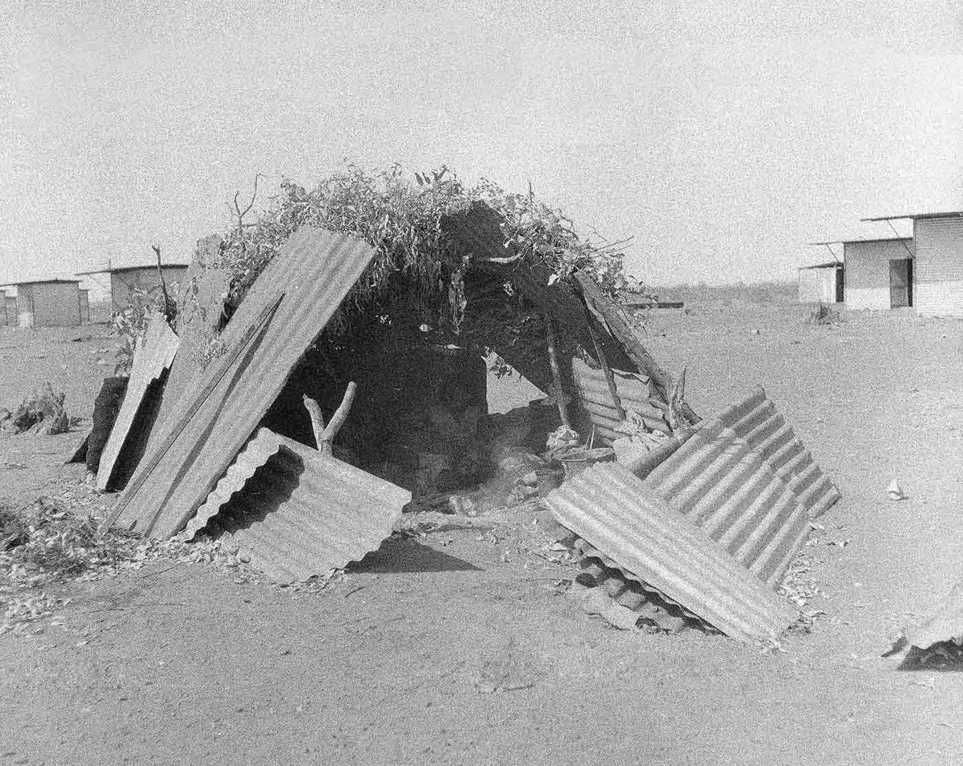 A black and white photo of a Warlpiri shelter with huts in the background.