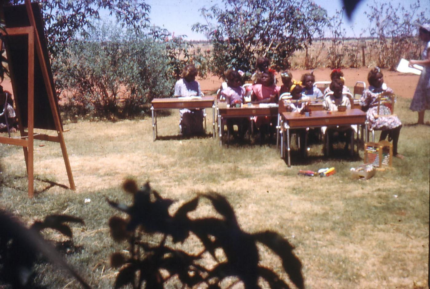 A group of children sitting at desks in an outdoor area.