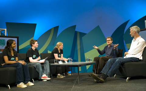 A middle distance image of three students on the left side of the image seated on brown sofa-like chairs facing John Safran and David Pope on the right side of the image seated on the same type of chair. A small table with glasses of water is in the middle of the image. The background is in shades of blues and greens.