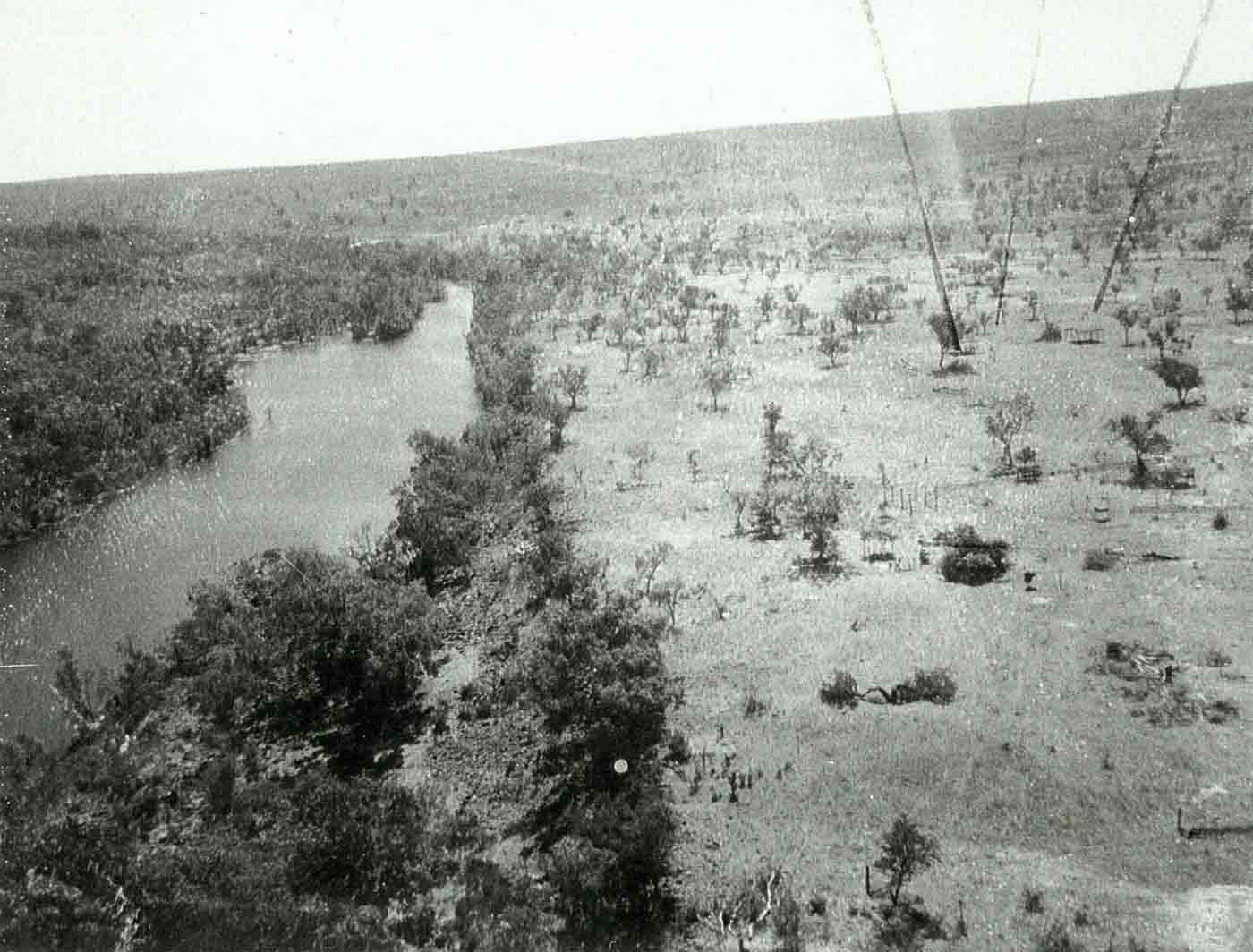 Black and white photo of an aerial view of a river lined with trees and sparse bush land beyond.