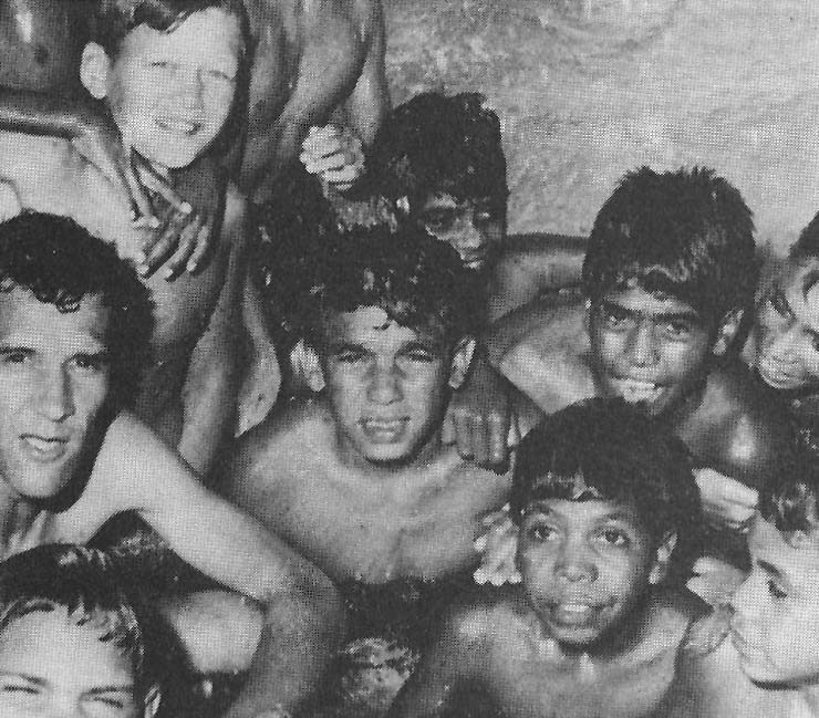 Black and white photo of a man with boys who are posing in between swimming.