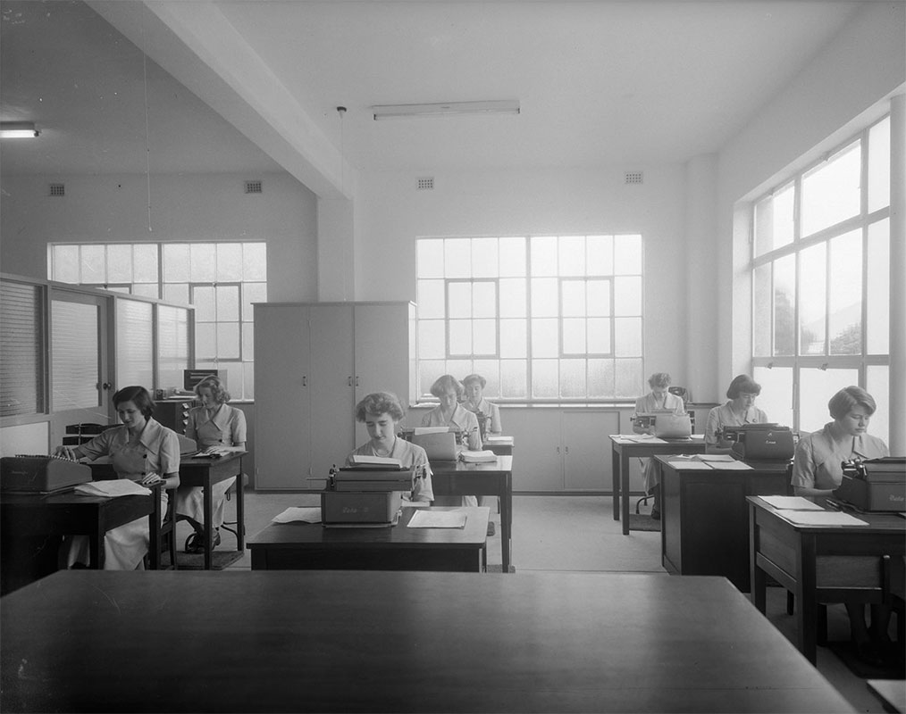 A black and white photograph of eight young women sitting at individual desks working on tabulating machines and typewriters. There are sheets of paper on each desk. The women are dressed identically in short-sleeved uniform dresses. They are seated in three rows with two in the left row working on tabulating machines, and three in both the centre and right hand rows working on typewriters. On the left is a partitioning half-wall that has frosted glass sections on top. There is a door in the partition that is closed. Built-in cupboards line the back wall and there is a telephone in the back right hand corner on top of the cupboard. Light is entering the room from three large windows. There is a fluorescent light above the women that is off, and part of another light, which is switched on, is visible on the left beyond the partition. - click to view larger image