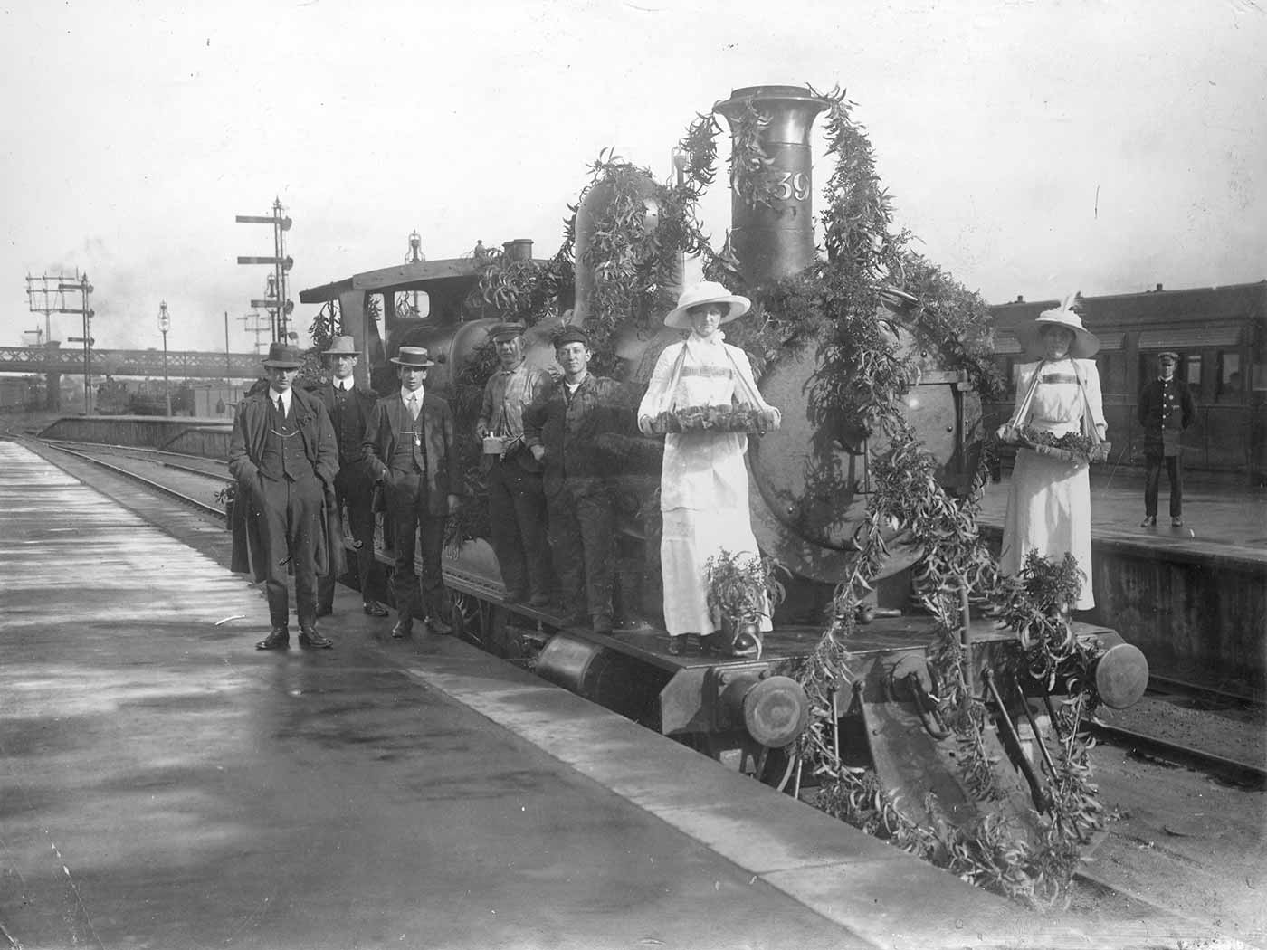 Train engine adorned with plant material. A group of people stand in front of and beside the engine.