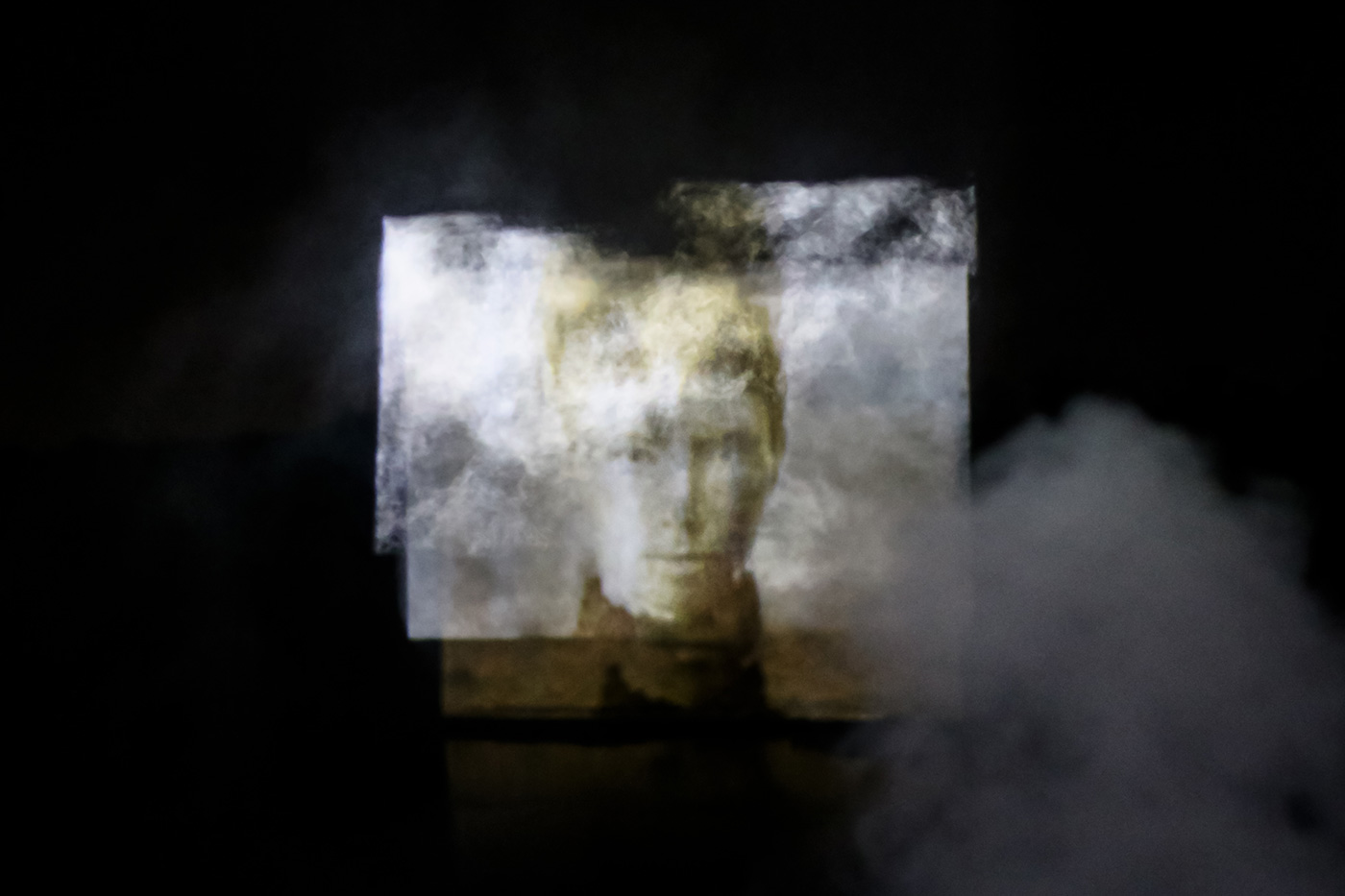 An artist's work which projects the face of a historic photo over a large screen. Fog or smoke appears in the bottom right-hand corner and there is also some appearing over the top of the projecting which seems to distort the image slightly, however the face can still be seen. - click to view larger image