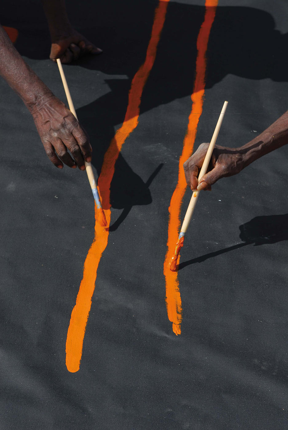 Colour photo of two hands painting orange pigment with onto a canvas. - click to view larger image