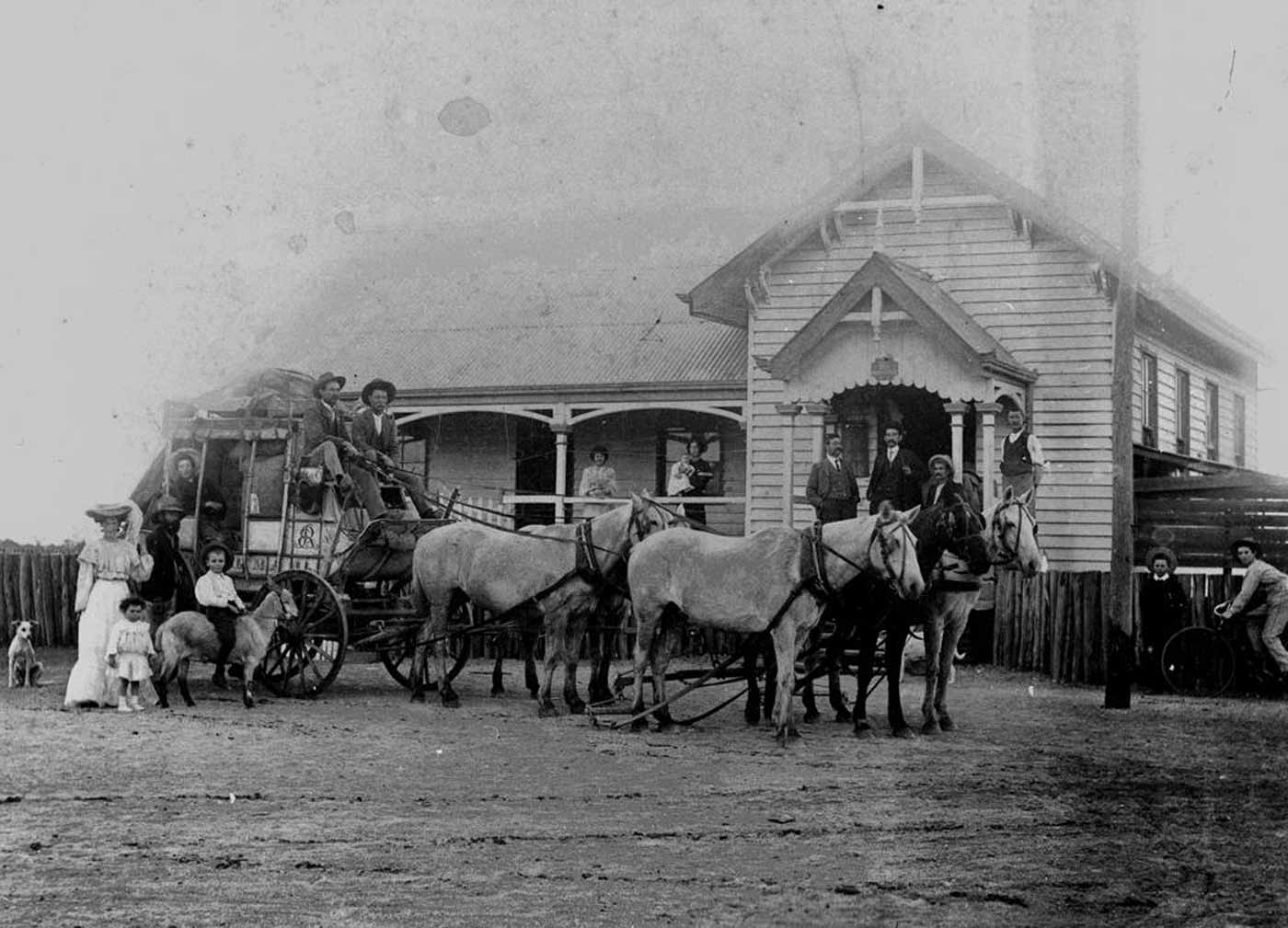 Black and white photo showing two men sitting at the front of a horsedrawn carriage. A person sits looking out a rear window of the carriage, which is loaded inside and on top with goods. A small child riding a goat stands alongside, with a man, woman and another child. Several people stand behind on the verandah of a weatherboard building. - click to view larger image