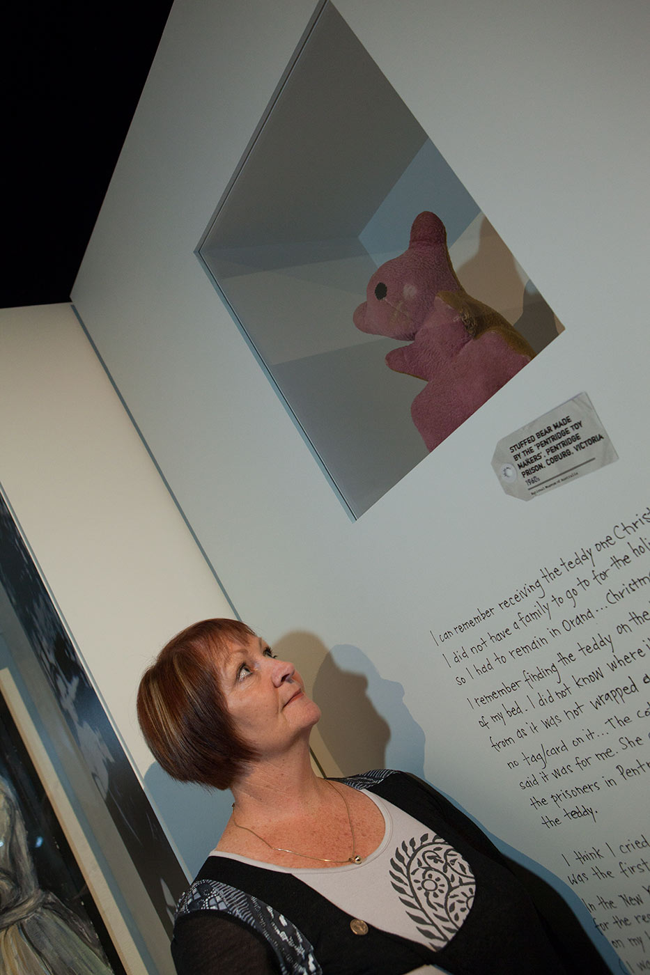 Colour photograph showing a woman standing beside an exhibition panel, gazing up at a small pink bear on display. - click to view larger image