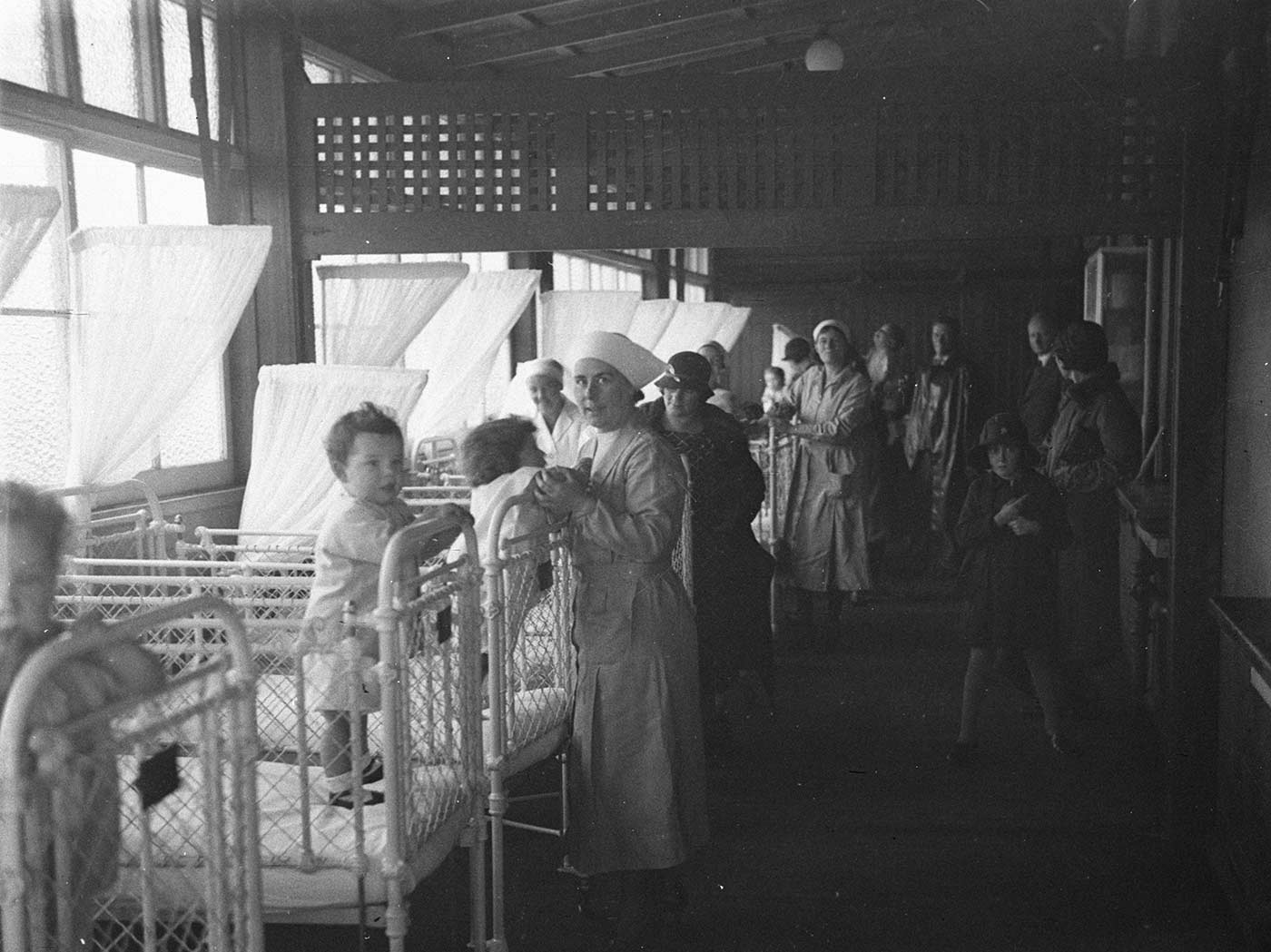 Black and white image showing a row of metal and wire framed cots, painted white, at left. Three young children stand in the cots closest to the camera. A nurse stands near the third. Other children, cots and people stand in the background. - click to view larger image