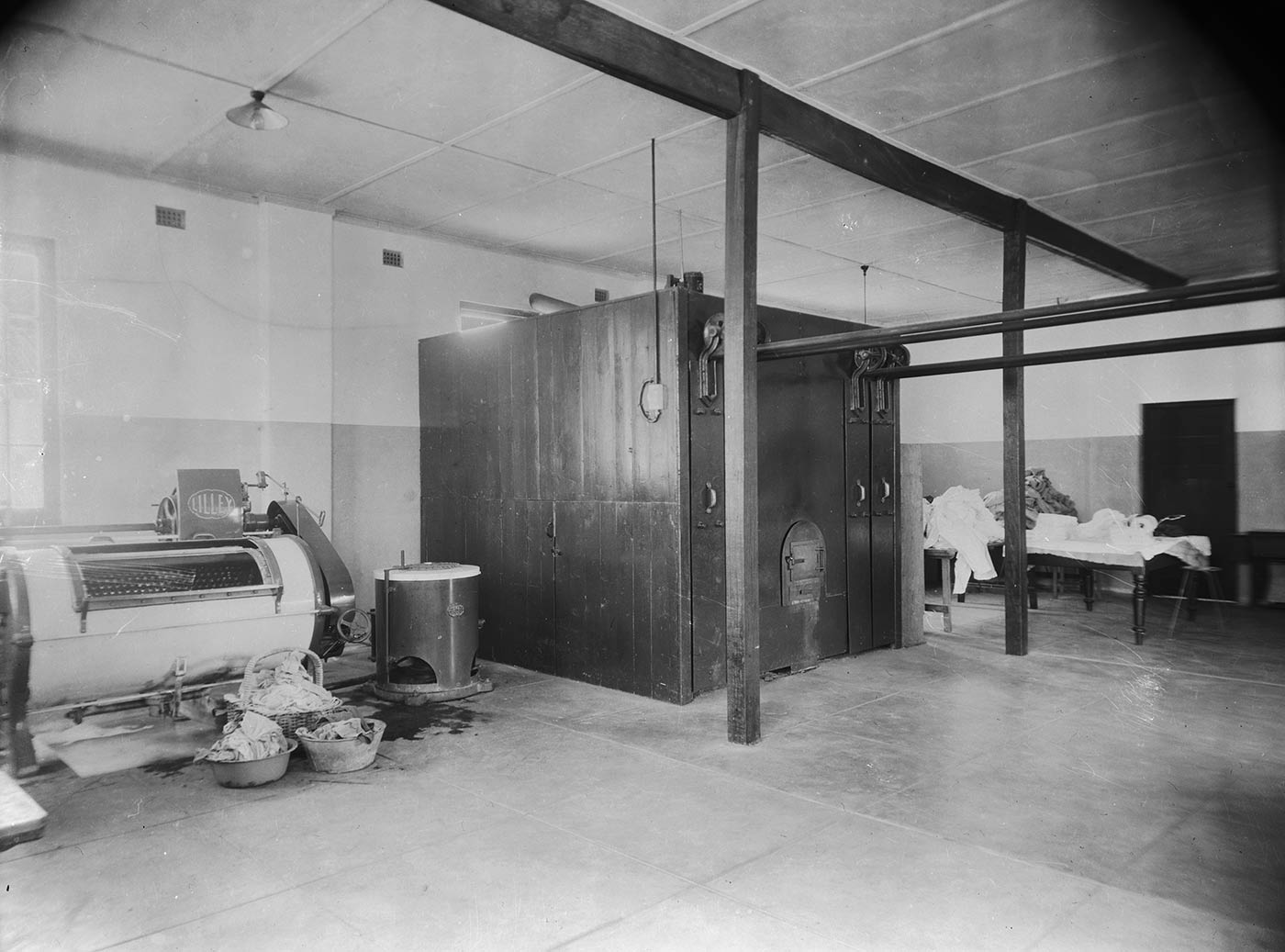 Black and white photograph showing a large commercial laundry, with baskets of wet clothes near a large wringer. - click to view larger image