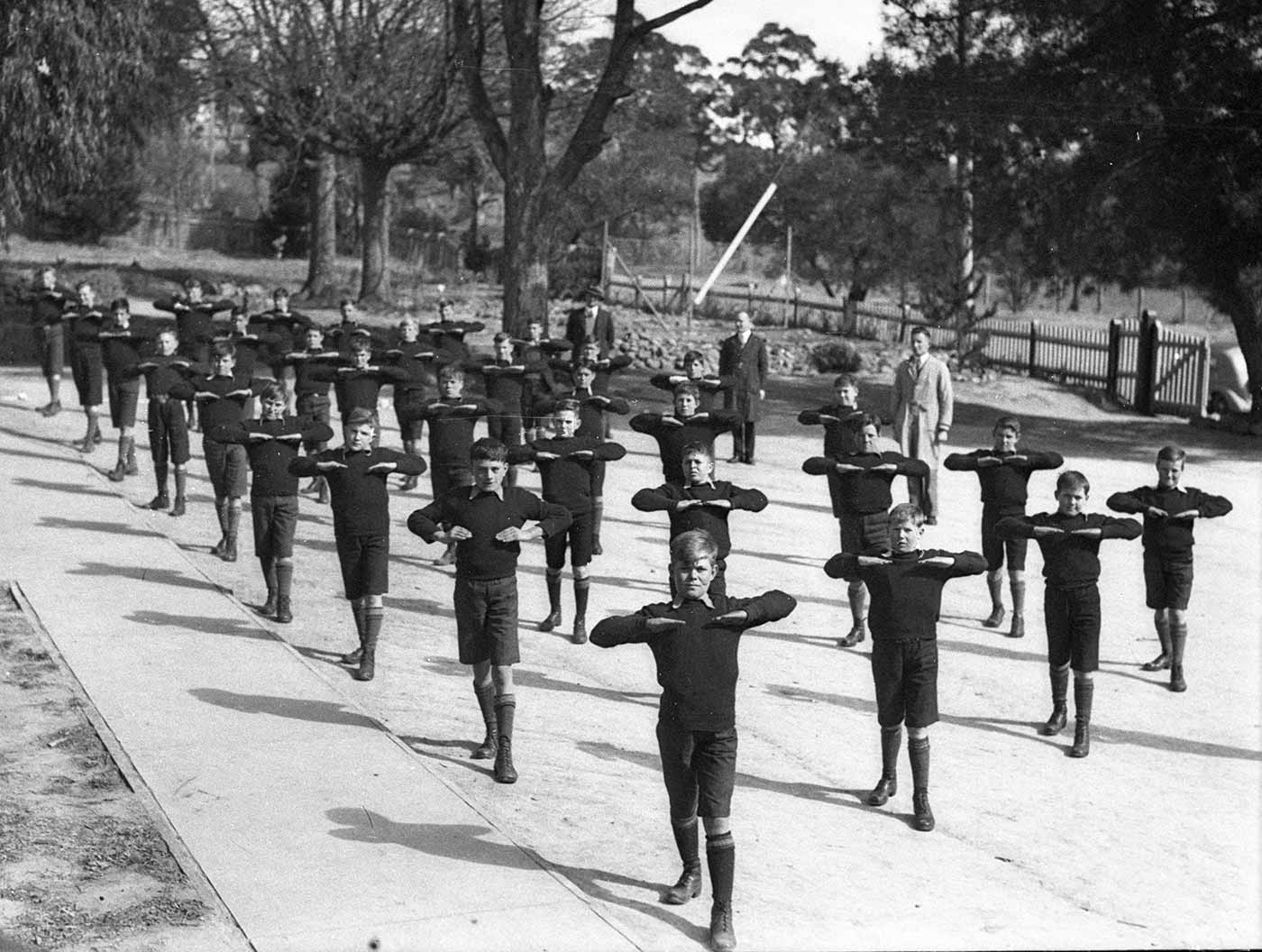 Black and white photograph showing nine rows of four boys standing outside with right leg extended forward and arms raised to chest height, with hands pointing down. The boys wear matching dark shorts, jumpers, long socks and boots. Three men stand behind them towards the back of the photo. - click to view larger image