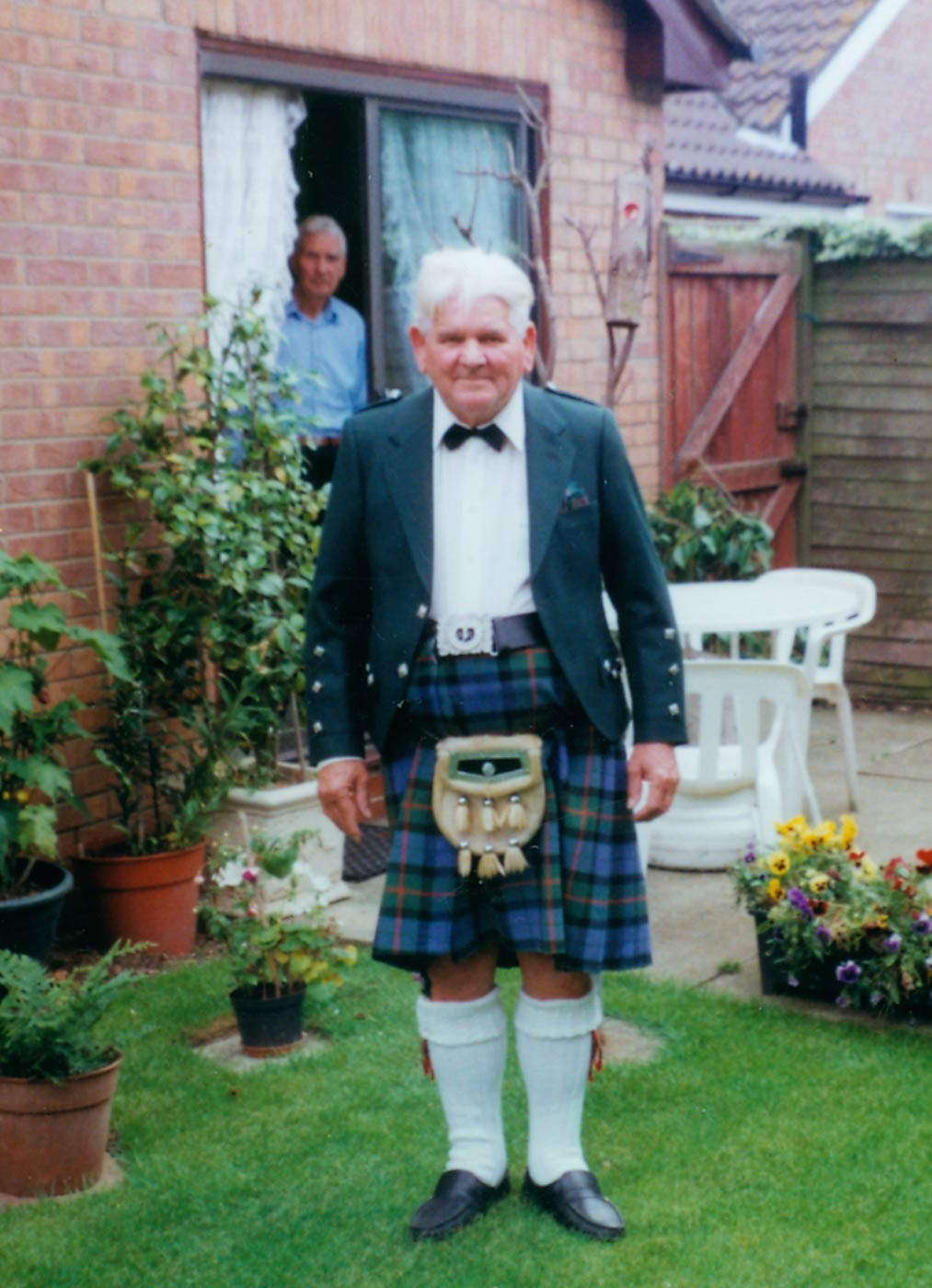 Colour photograph of a man standing in a garden outside a house. He wears traditional Scottish dress of a tartan kilt, sporran and tailored jacket. - click to view larger image