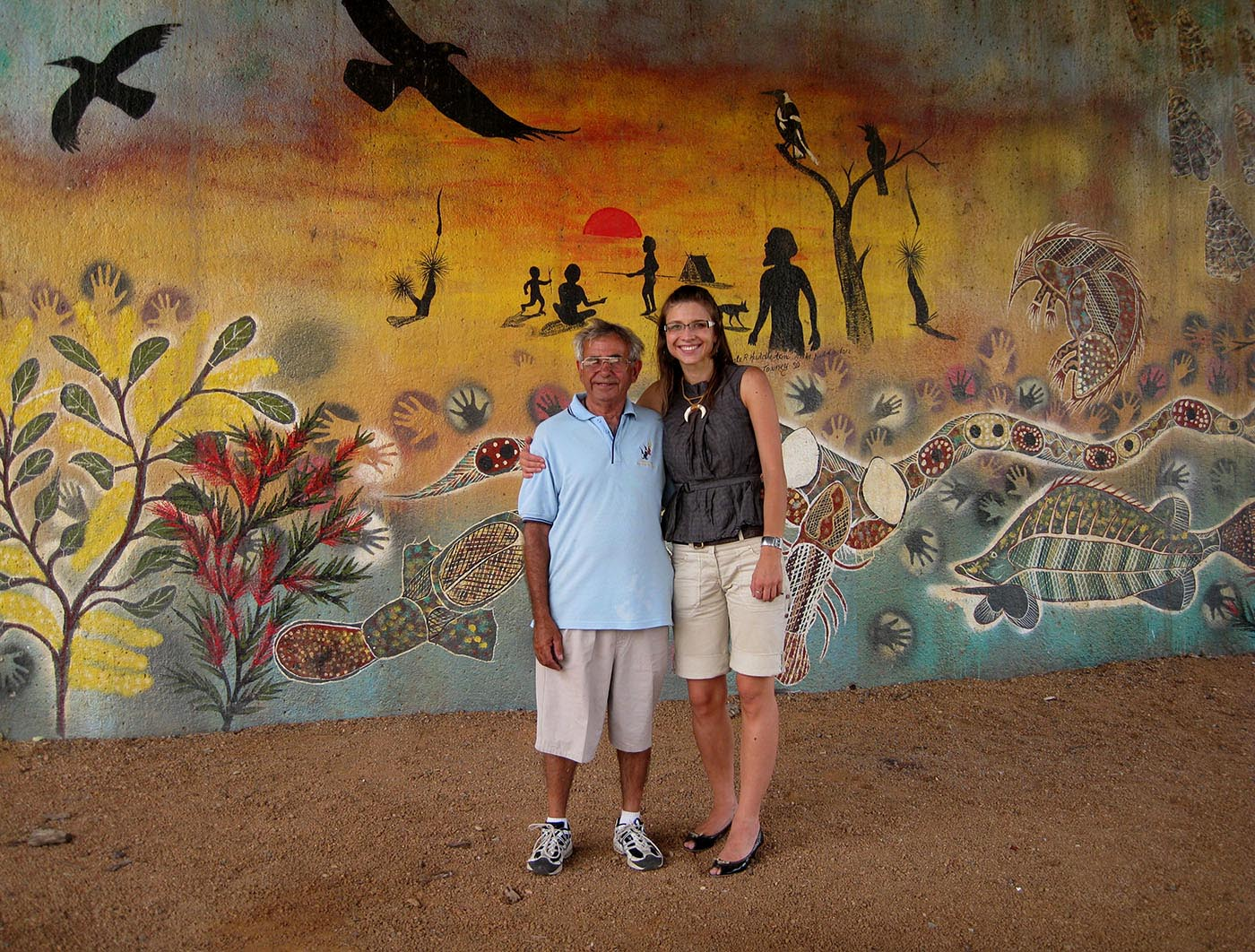 Eric Bell and Karolina Kilian stand in front of a large mural of Aboriginal motifs.