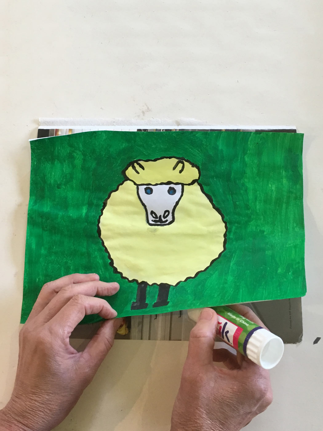 A pair of hands gluing down an illustration of a sheep on paper created with textas and paint.