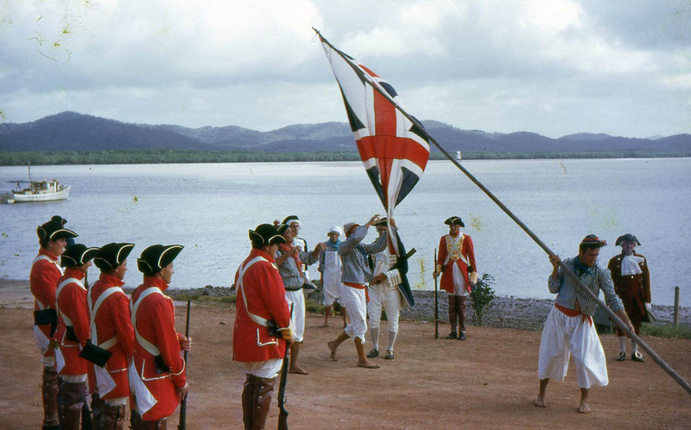 Colour photo of men in costume beside a large river and raising the British flag. - click to view larger image