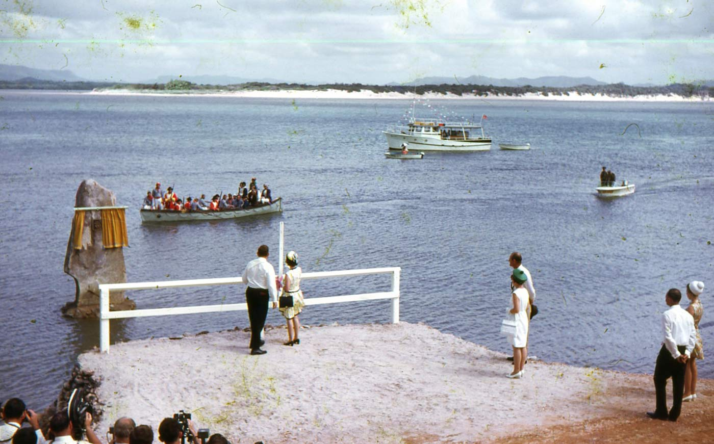 Colour photo of Queen Elizabeth II attempting to draw curtains using a rope attached that is covering a plaque fixed to a rock. The rock is on the Endeavour River and there is a rowboat with men in periodic costume looking on. There are camera crew filming and taking photos in the foreground. - click to view larger image