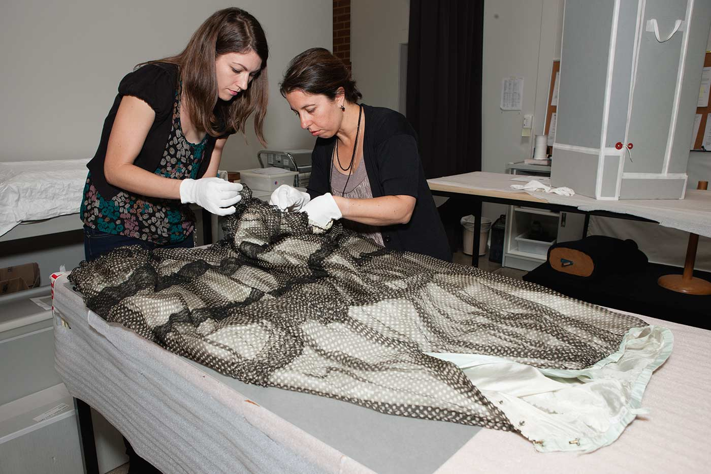 Two conservators prepare a skirt. - click to view larger image