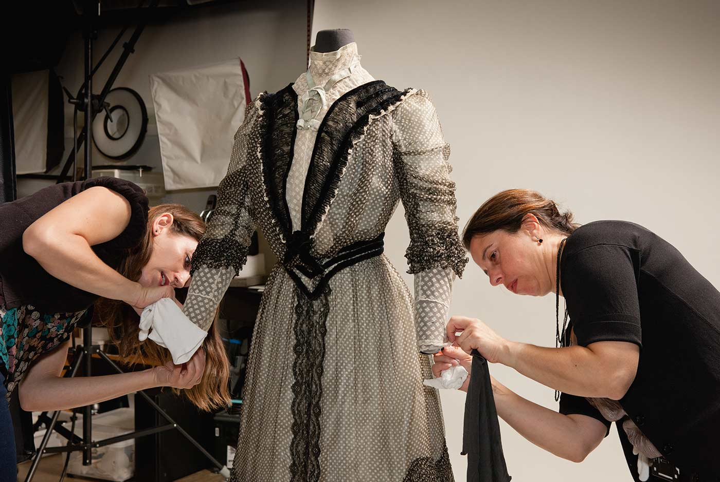 Two conservators are working on a dress.