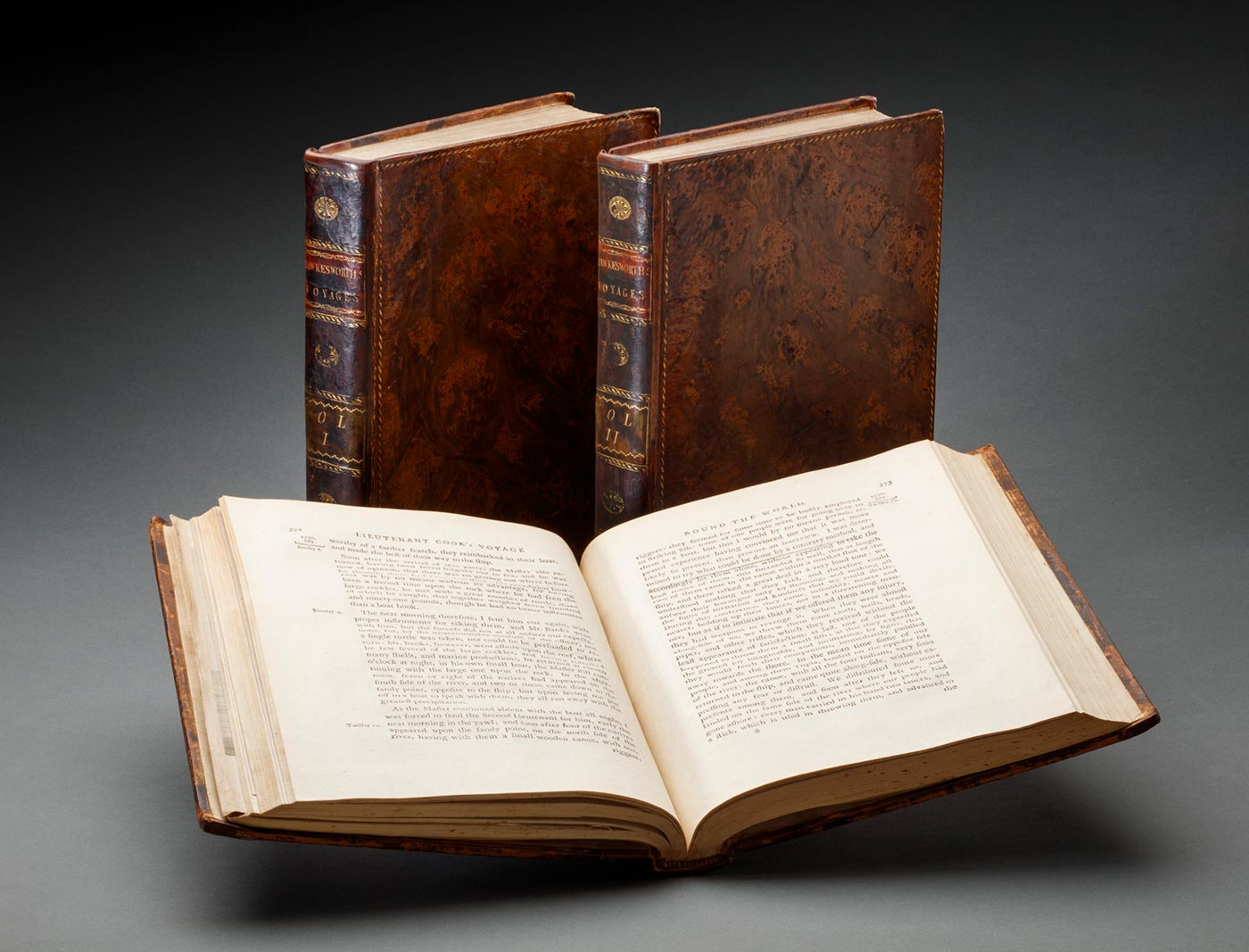 Three hardcover, leather bound volumes of a book. One is open about half way through. - click to view larger image