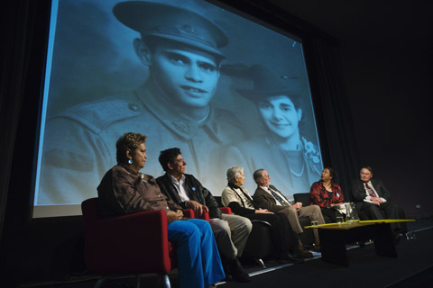 Six members of the forum panel seated on stage with a large image of a young soldier and a woman on a screen behind them.