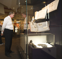 Man looking into a clear glass cabinet which contains a photograph album and other objects.