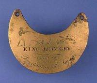 Crescent-shaped breastplate inscribed 'King John Cry, Chief of the Duedolgongtule, Argyle', with an image of a man aiming a gun at a small animal.