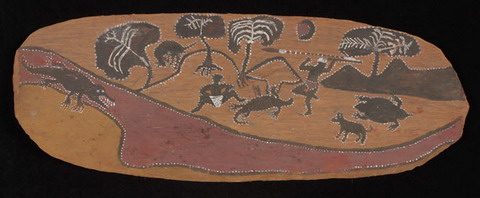 Ochres on an oval shaped bark panel depicting a camping scene with trees, low hills and a stream. A kangaroo, lizard, echidna, a dog and two human figures feature in the landscape, one of whom is about to throw a spear at a large crocodile in the stream.