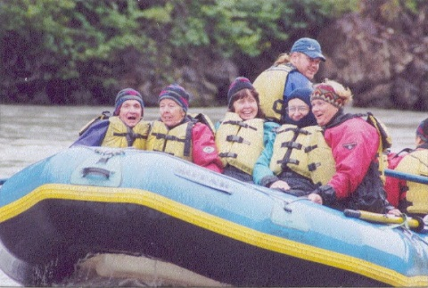 Colour photograph showing six people in an inflatable raft on a river. Five people wearing life jackets sit facing the front of the raft. A man with a ponytail sits higher, towards the rear of the raft. A seventh person is partially visible on the right.