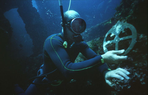A diver under water holding an astrolabe.