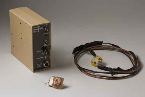 Small bionic ear implant, with coiled cables inside, pictured with a box marked 'Speech Processor PSP-2' and a small receiver unit attached to coiled cables and a velco headstrap.
