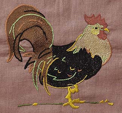 Close up quilt detail of a rooster embroidered in one of the squares.