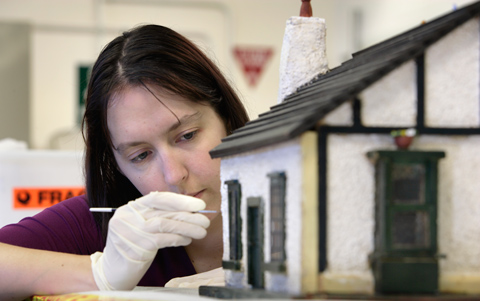 Museum conservator applying an adhesive to the outside walls of the doll's house.