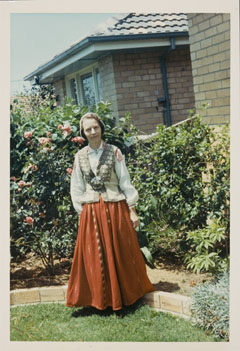 Colour photograph showing a woman dressed in Latvian national costume, consisting of a red skirt, beige waistcoat, white shirt and cloth cap. The woman stands in a suburban garden.