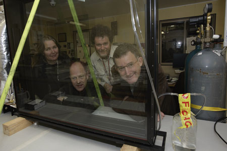 Conservation team members peer through the new glass case, with gas cylinder off to the side, in the laboratory