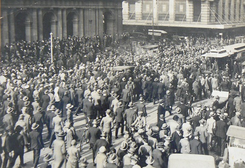 Black and white photograph showing a crowd of people in a city street.