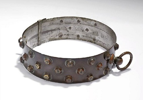 Copper patinated circular collar with raised studs on the outside and a small ring attached at the seam.
