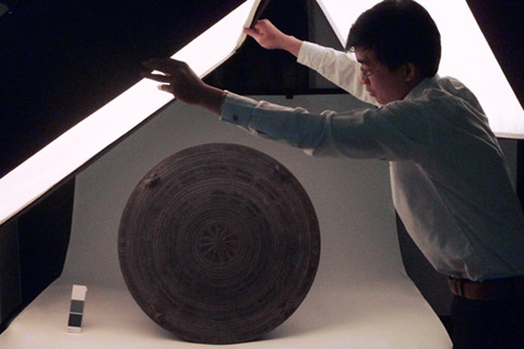 Mr Phoxay Inkong, Assistant Research and Exhibitions, moves lighting into position for detailed photography of musical drum.