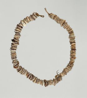 Necklace made from small worn olive nut shells strung together on a cord made of a plant material.