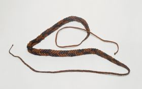 Rope made of reddish-brown and blackish-brown coconut fibre cords plaited together several times.