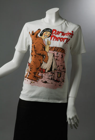 Souvenir T-shirt which reads 'Darwin's Theory' and shows a woman resembling Lindy Chamberlain giving the thumbs up while holding a dingo skin, outside a tent.