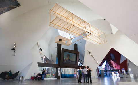 A replica of a biplane (two wing) glider suspended from the ceiling of a hall in a museum. The glider is made from wood and fabric. A small group of people stand under the glider looking up at at.