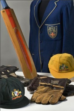 Cricket bat, blue blazer, caps and gloves.