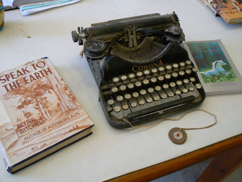 An old-fashioned typewriter on a desk. The typewriter has round keys and the word 'Corona' on the front of the mechanism casing. A piece of string is tied to the front of the typewriter; a disc with a hole in it is attached to the other end of the string. Two books are next to the typewriter. The book at left is called Speak To The Earth while the book at right is called The Silver Brumby.