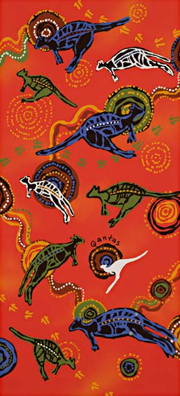The design features several X-ray style kangaroos in green, blue and black, in various orientations, and concentric circles. The background is bright mottled orange. There is also a grey Qantas logo kangaroo just below the centre.