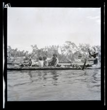 A black and white photographic negative that depicts an Aboriginal man wearing a hat paddling a canoe along a river with a dog and four passengers sitting in the canoe.