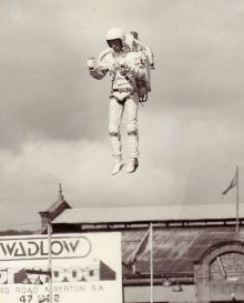 A man with a jetback on his back rises into the air. He wears a helmet and white suit.