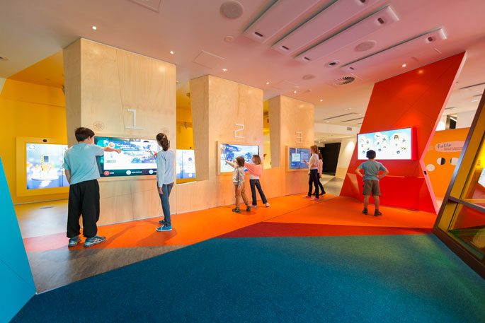 Children interacting with touch screens in the Cool-down area in Kspace.