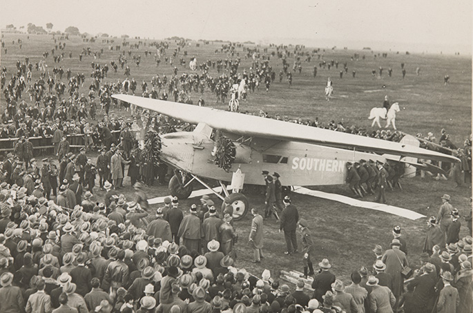An aeroplane on the ground surrounded by a large crowd of people.